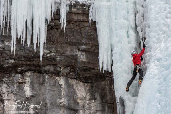 ice climber in red jacket in johnston canyon