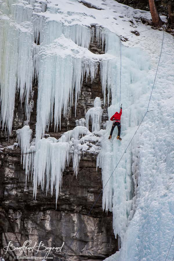 ice climber making his way down upper falls in johnstcon canyon