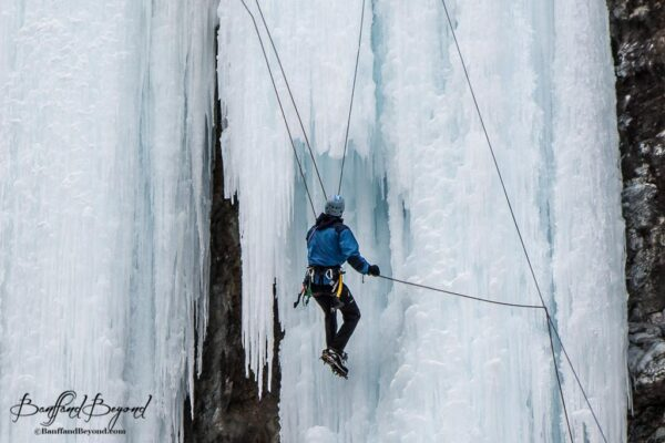 ice climber with ropes and harness in johnston canyon