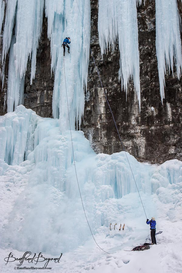 man guided saftey rope for ice climber in johnston canyon