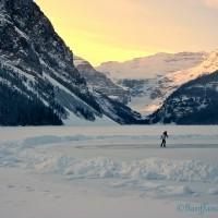 person skating on ice rink at lake louise at sunset