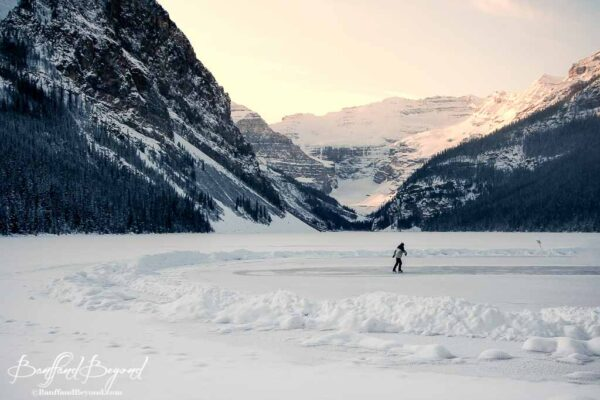 skater-gliding-across-lake-louise-ice-rink-sunset-beautiful-outdoor-scenery