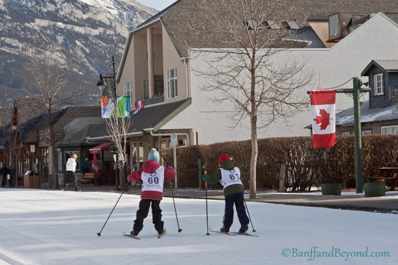 kids-cross-country-skiing-racing-main-street-canmore-winter-carnival-mountains-shops-downtown