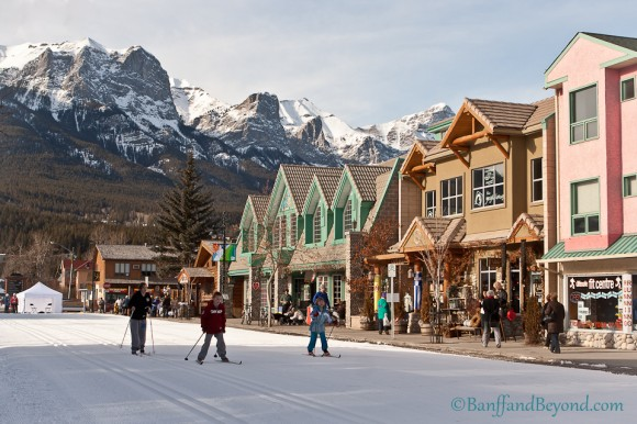 people-cross-country-skiing-nordic-canmore-winter-festival-main-street-snow-colorful-shops-mountains