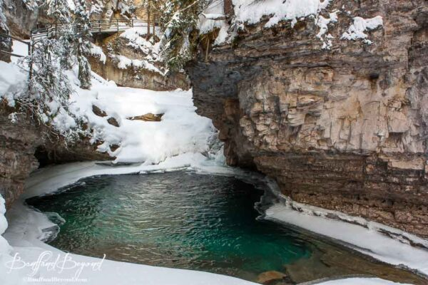pool of turquoise coloured water surrounded by snow in johnstcon canyon
