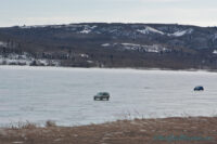 cars driving on frozen ghost lake in alberta foothills area