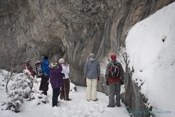 group-hikers-standing-ice-limestone-cliff-face-grotto-canyon-canmore-alberta-winter-outdoor-activity