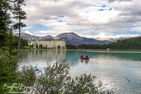 canoe floating towards chateau hotel on lake louise
