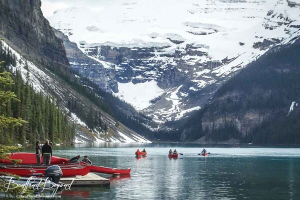 canoes on lake louise with victoria glacier in background