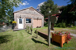 cute-house-red-flower-planter-yard-green-grass-trees-shrubs-garden-field-british-columbia-yoho-national-park