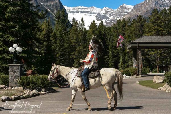 first nations person riding horse in lake louise canada parade