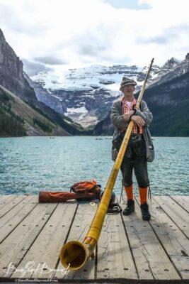 man playing traditional swiss alphorn at lake louise