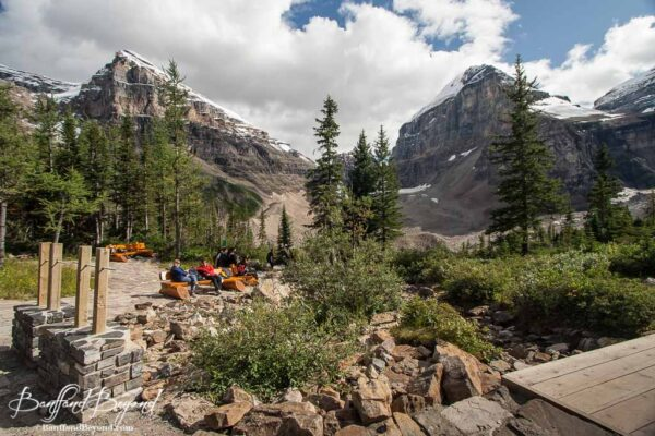 picnic tables and benches with mountain views near the plain of six glaciers tea house