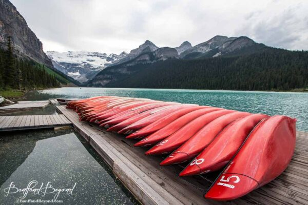red canoes lined up at dock at lake louise boathouse