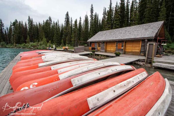 row of red canoes in front of fairmont chateau lake louise boathouse