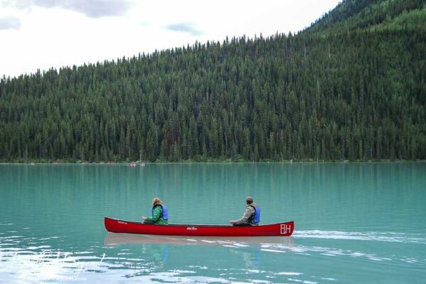 single canoe on turquoise waters of lake louise