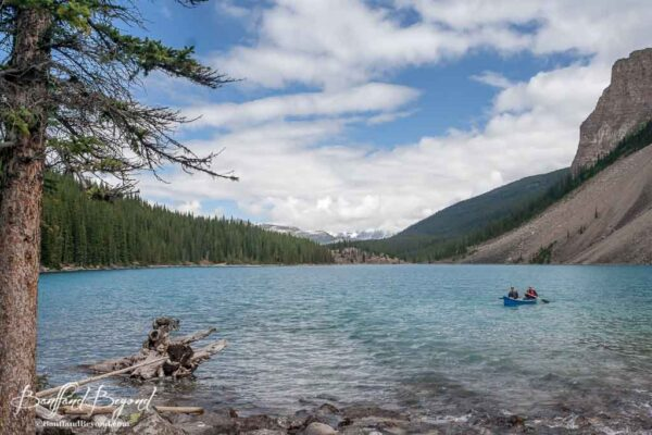 people paddling a canoe near the back of moraine lake