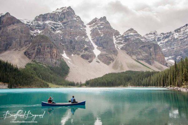 people paddling a canoe on moraine lake