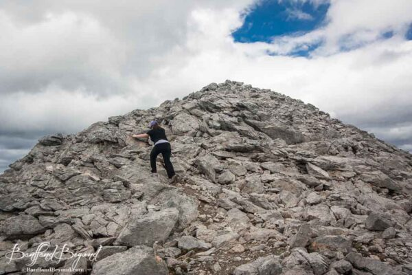 scrambling up the rock scree on the top of cavell meadow hike