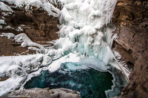 partially frozen lower falls at johnston canyon with blue water and ice