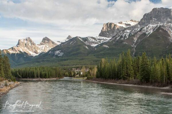 view of three sisters mountain range from the bow river in canmore