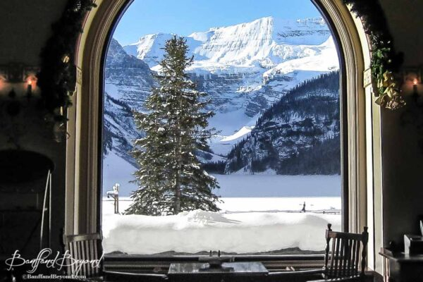 view of wintery lake louise from inside the fairmont chateau hotel restuaurant lounge
