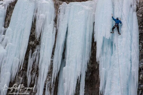 ice climber with axe in frozen waterfall